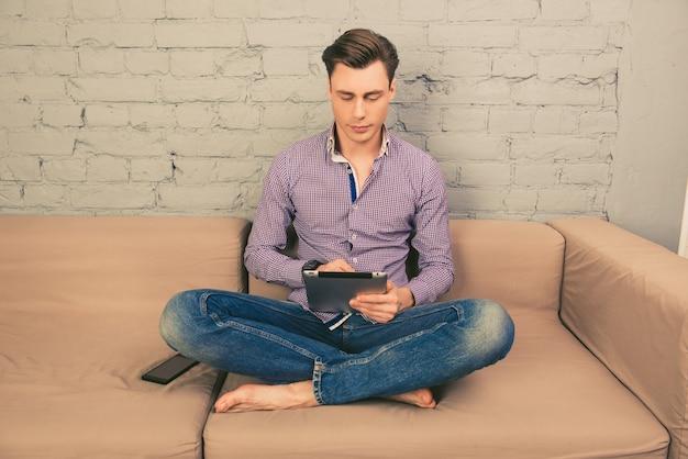 Porträt des mannes, der auf couch sitzt und digitales tablett verwendet
