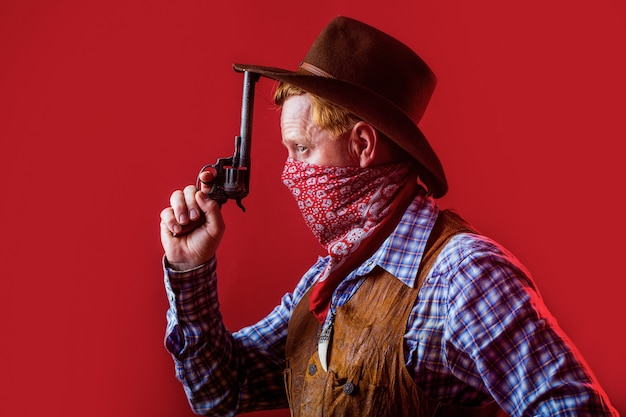 Porträt des mannes, der cowboyhut, waffe trägt. porträt eines cowboys. westen, waffen. porträt eines cowboys. amerikanischer bandit in maske, westlicher mann mit hut. porträt des cowboys im hut.