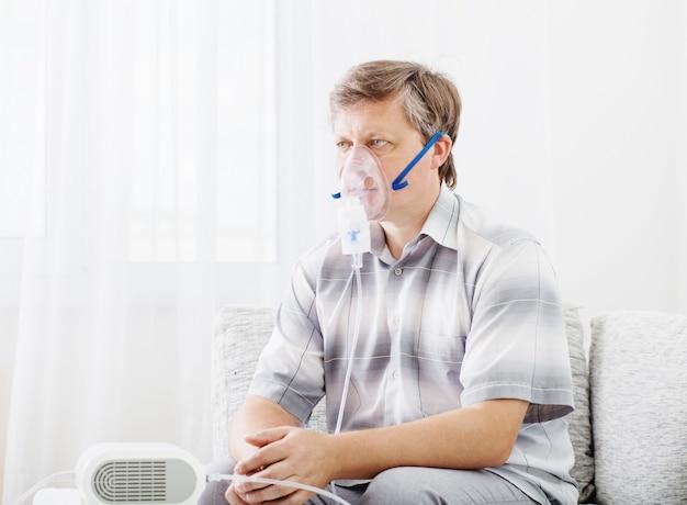 Porträt des mannes, der durch inhalatormaske einatmet