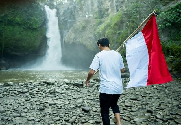 Porträt des mannes, der eine flagge von indonesien hält. feier zum unabhängigkeitstag