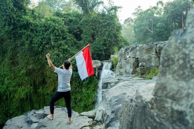 Porträt des mannes, der eine flagge von indonesien hält