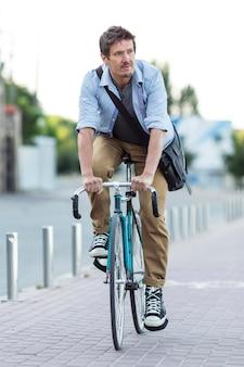 Porträt des mannes, der fahrrad in der stadt reitet