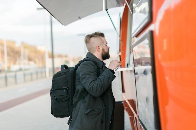 Porträt des mannes, der fast food im food truck in der streetfood-food-industrie und streetfood wählt