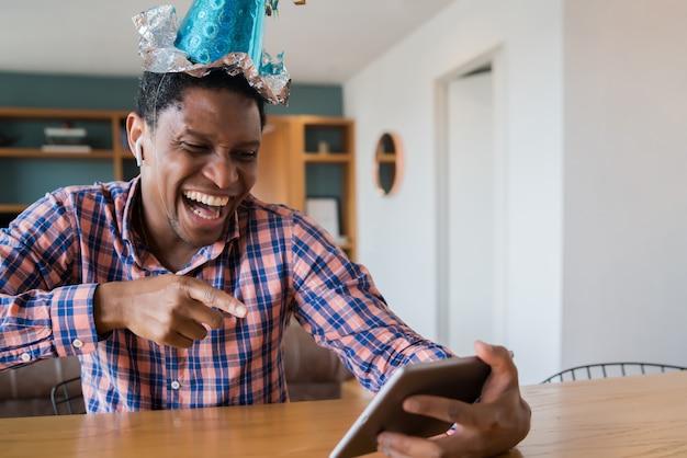 Porträt des mannes, der geburtstag auf einem videoanruf mit digitalem tablett zu hause feiert. neues normales lebensstilkonzept.