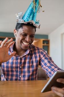 Porträt des mannes, der geburtstag auf einem videoanruf mit digitalem tablett zu hause feiert.