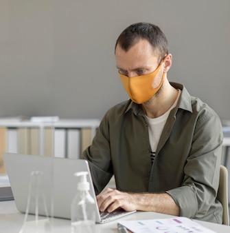 Porträt des mannes, der gesichtsmaske bei der arbeit trägt