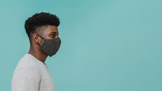 Porträt des mannes, der gesichtsmaske mit kopienraum trägt