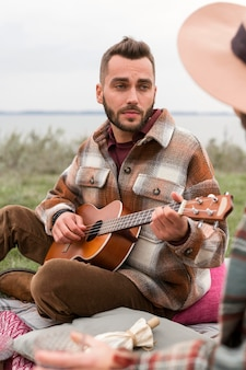 Porträt des mannes, der gitarre für freundin spielt
