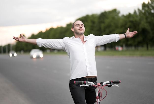 Porträt des mannes, der glücklich ist, fahrrad auf der straße zu fahren