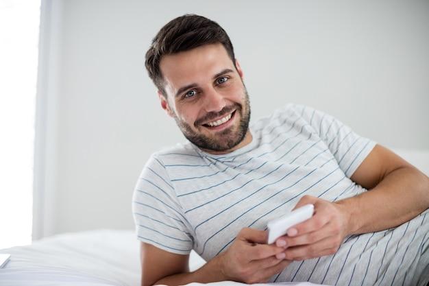 Porträt des mannes, der handy auf bett im schlafzimmer benutzt