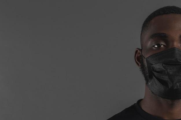 Porträt des mannes, der maskenkopierraum trägt