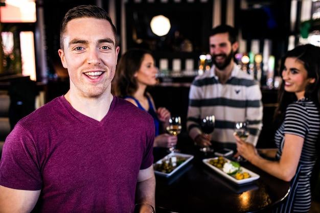 Porträt des mannes, der mit freunden in einer bar etwas trinkt