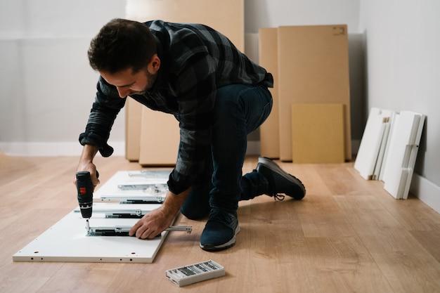 Porträt des mannes, der möbel zusammenbaut. machen sie es sich selbst möbelmontage.