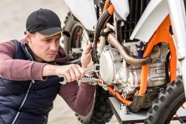 Porträt des mannes, der motorrad im freien repariert