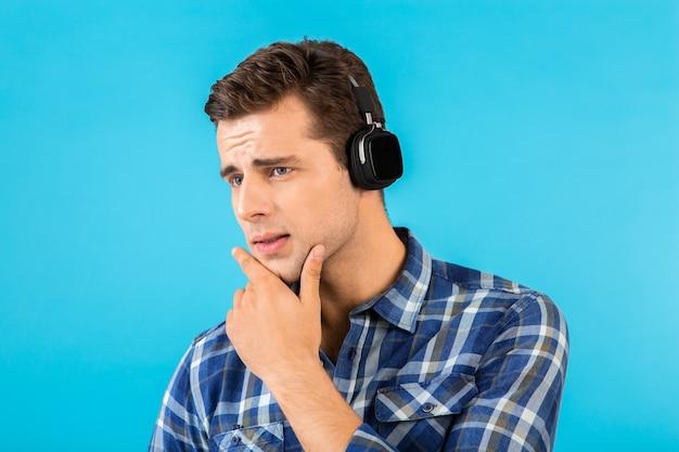 Porträt des mannes, der musik auf kabellosen kopfhörern hört, die spaß auf blau haben