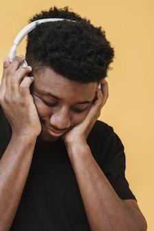 Porträt des mannes, der musik über kopfhörer hört