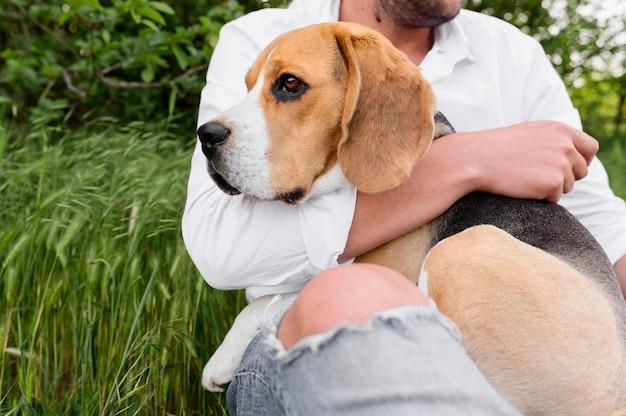 Porträt des mannes, der niedlichen kleinen hund hält