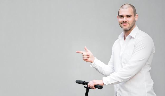 Porträt des mannes, der roller mit kopierraum reitet