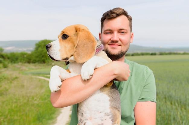 Porträt des mannes, der seinen entzückenden hund hält