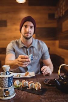 Porträt des mannes, der tasse zeigt
