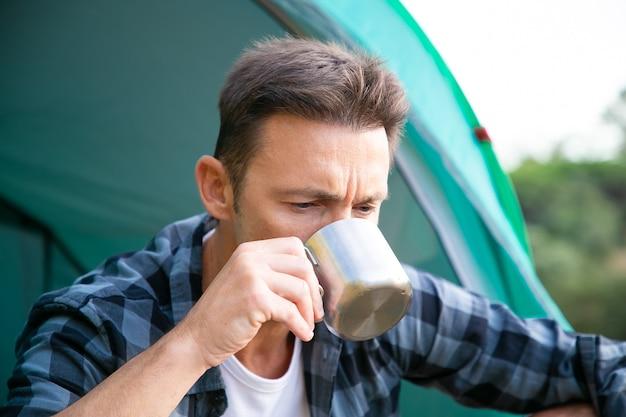 Porträt des mannes, der tee trinkt, im zelt sitzt und denkt. kaukasischer attraktiver männlicher tourist, der allein sitzt und metallbecher hält. tourismus-, abenteuer- und sommerferienkonzept