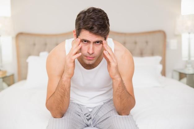 Porträt des mannes, der unter kopfschmerzen im bett leidet