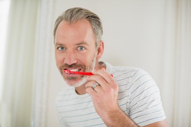 Porträt des mannes, der zähne im badezimmer putzt