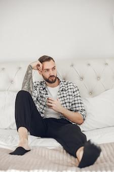 Porträt des mannes, der zu hause mit smartphone entspannt