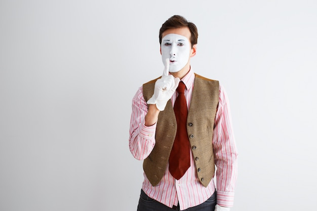 Porträt des mannes, des schauspielers, der pantomime, des mannes, der fingerfeste leiser macht.
