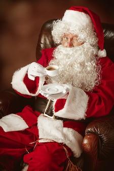 Porträt des mannes im weihnachtsmann-kostüm - mit einem luxuriösen weißen bart, der weihnachtsmann-mütze und einem roten kostüm am roten studiohintergrund, der in einem stuhl mit tasse kaffee sitzt