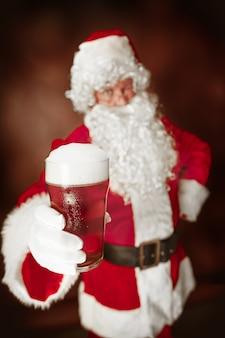 Porträt des mannes im weihnachtsmann-kostüm - mit einem luxuriösen weißen bart, der weihnachtsmann-mütze und einem roten kostüm am roten studiohintergrund mit bier