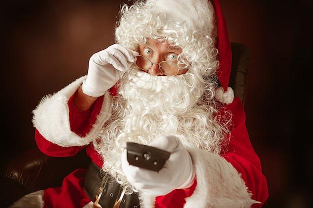 Porträt des mannes im weihnachtsmann mit einem luxuriösen weißen bart, der weihnachtsmannmütze und einem roten kostüm am roten studiohintergrund