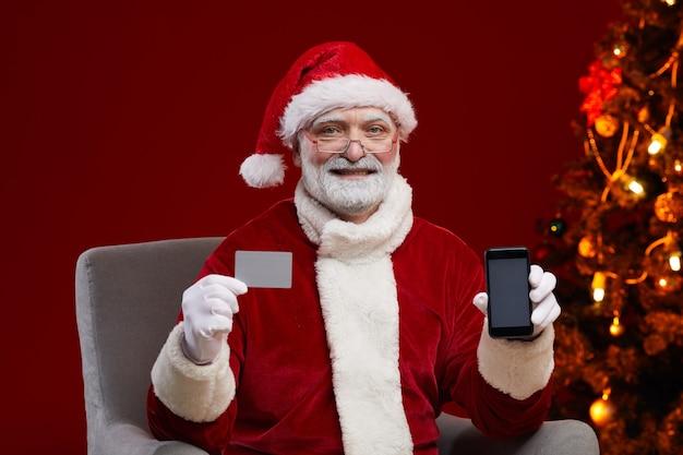Porträt des mannes im weihnachtsmannkostüm, das visitenkarte und handy in seinen händen hält