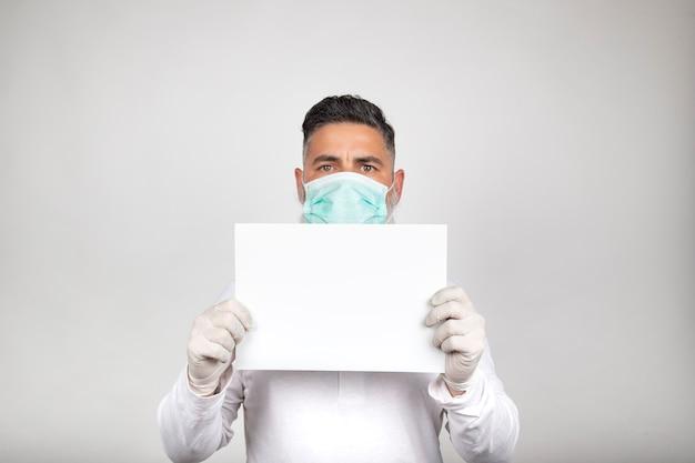 Porträt des mannes in der chirurgischen maske, die ein weißes zeichen auf weißem hintergrund hält.