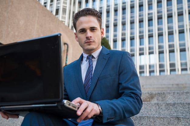 Porträt des mannes in der eleganten klage, die an treppe mit laptop auf knien arbeitet.