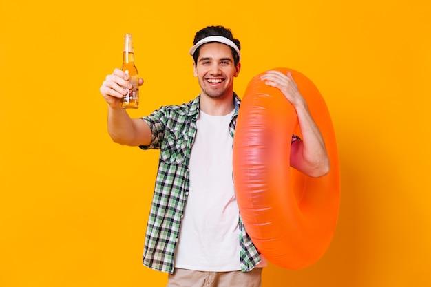 Porträt des mannes in der kappe, im hemd und im t-shirt, die flasche bier und aufblasbaren kreis auf isoliertem raum halten.