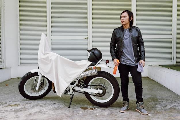 Porträt des mannes in der lederjacke, die mit dem poliermittel spreay an seinem fahrrad bedeckt durch überwurf steht