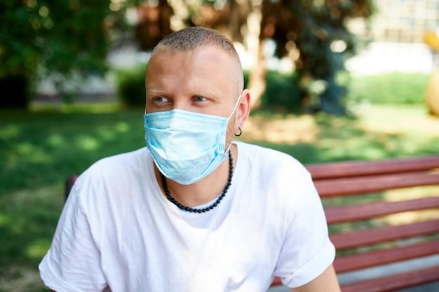 Porträt des mannes in der schutzmaske im park im freien in der stadt, konzept selbstpflege, leben während der coronavirus-pandemie, über quarantäne, stop covid-19, kehren zum normalen leben zurück.