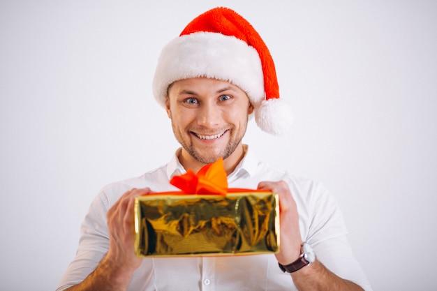 Porträt des mannes in sankt-hut, der weihnachtsgoldenen präsentkarton hält