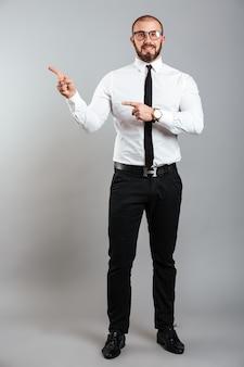 Porträt des mannes in voller länge des mannes in der brille im sachlichen anzug, der auf der kamera aufwirft und finger beiseite auf kopienraum zeigt, lokalisiert über graue wand