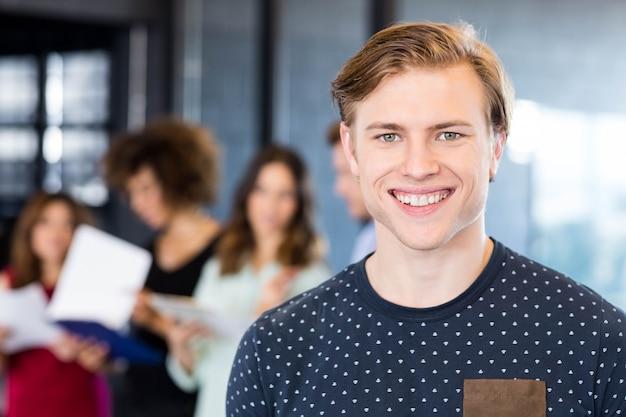 Porträt des mannes lächelnd im büro während ihre kollegen, die hinten im büro stehen