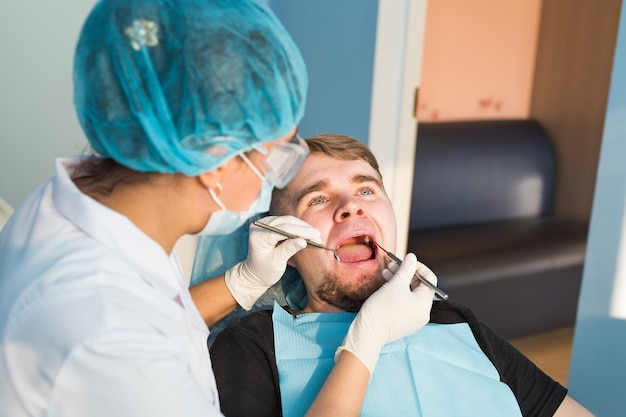 Porträt des mannes. lächelndes gesicht. zahnpflege-konzept. zahnärztliche untersuchung wird einem schönen mann gegeben, der von einem zahnarzt umgeben ist.