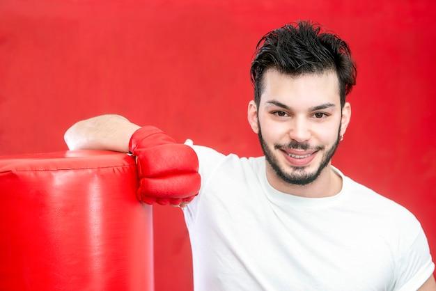 Porträt des mannes mit bartboxer im training auf einem boxsack in einer turnhalle