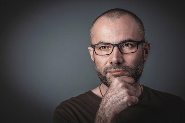 Porträt des mannes mit brille und hand am kinn.