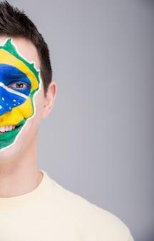 Porträt des mannes mit der brasilianischen flagge gemalt auf seinem gesicht.