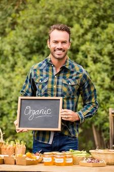 Porträt des mannes mit der tafel, die gemüse verkauft