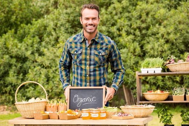 Porträt des mannes mit der tafel, die organisches gemüse verkauft