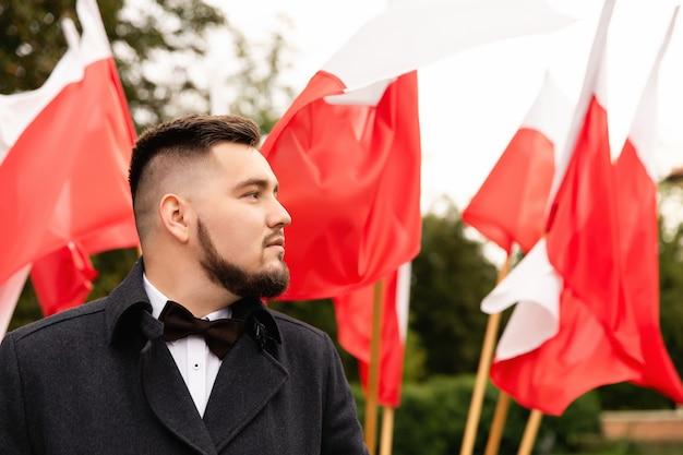 Porträt des mannes mit flaggen von polen dahinter