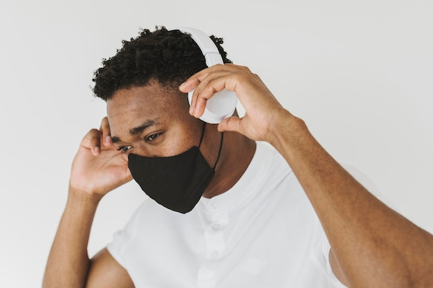 Porträt des mannes mit gesichtsmaske, die musik auf kopfhörern hört