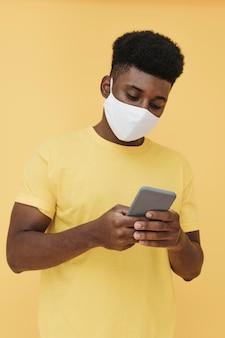 Porträt des mannes mit gesichtsmaske, die smartphone hält